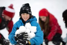 A young person holds a pile of snowballs while playing with others in the snow.