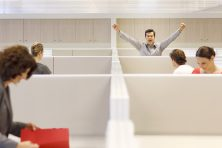 Businessman cheering in cubicle
