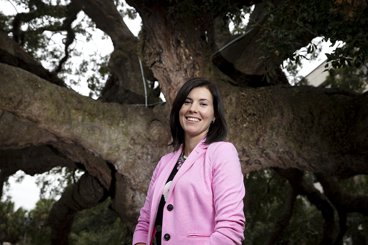 A woman poses for portraits outside of Treaty Oak, a tree where its limbs touch the ground, in Jacksonville, Fla.