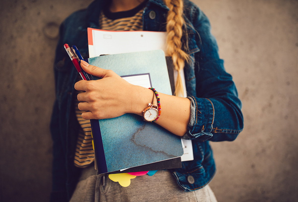 Close-up of hipster woman attending college holding books, notebooks and pens