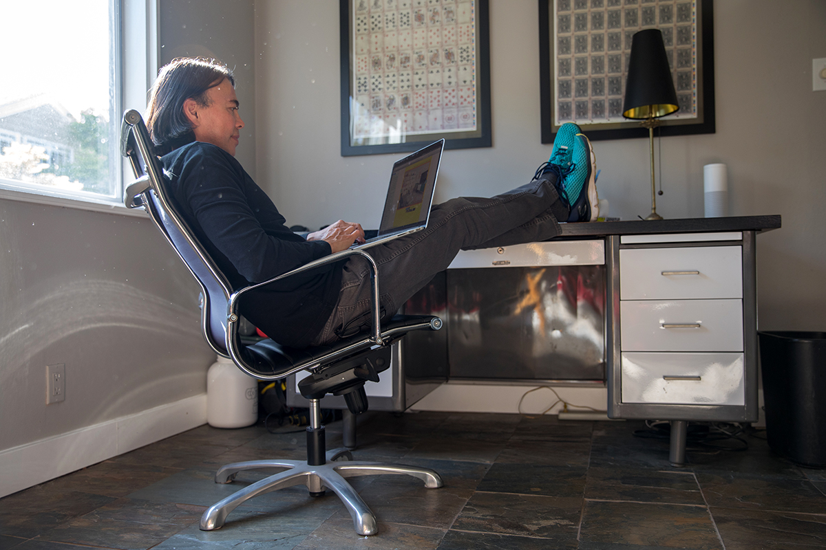 Terence Michael, a Hollywood producer, sits at his desk in his home in Los Angeles. He also makes extra income as an Airbnb super host.