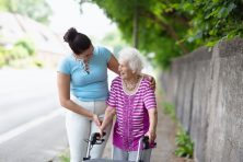 Young woman helping senior woman walking in the street