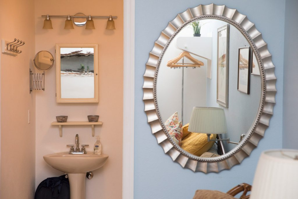 A bathroom is photographed with the bedroom reflected in the mirror. If you have a spare bedroom, try listing it on Airbnb to make some extra cash.