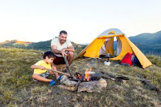 A father and son camp in the wilderness.