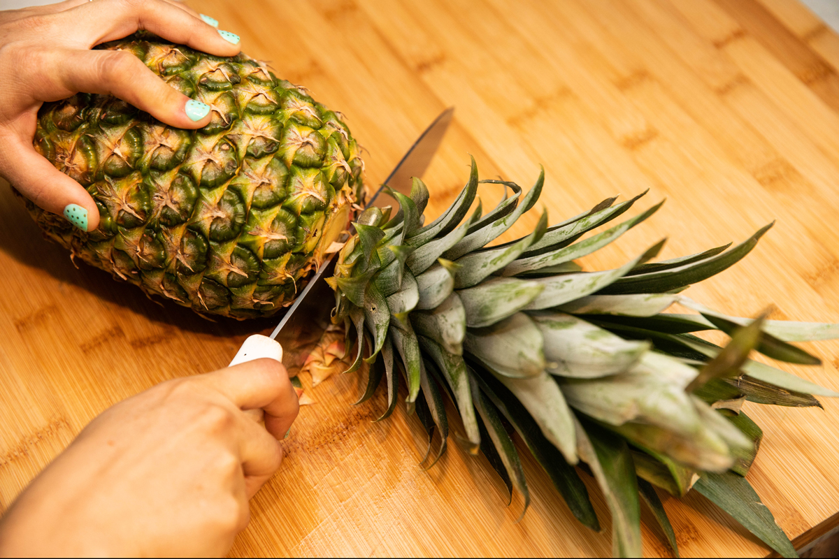 A person cuts into a pineapple.