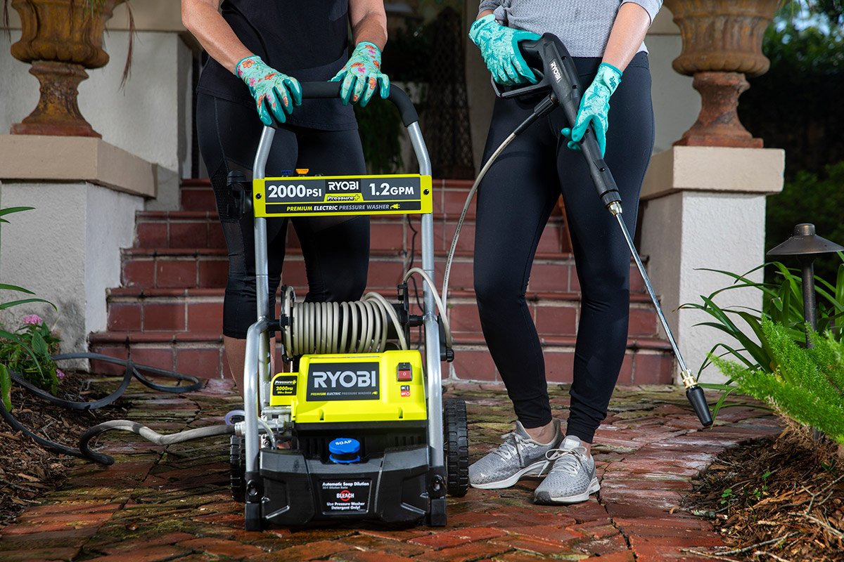 two women stand next to a pressure washer