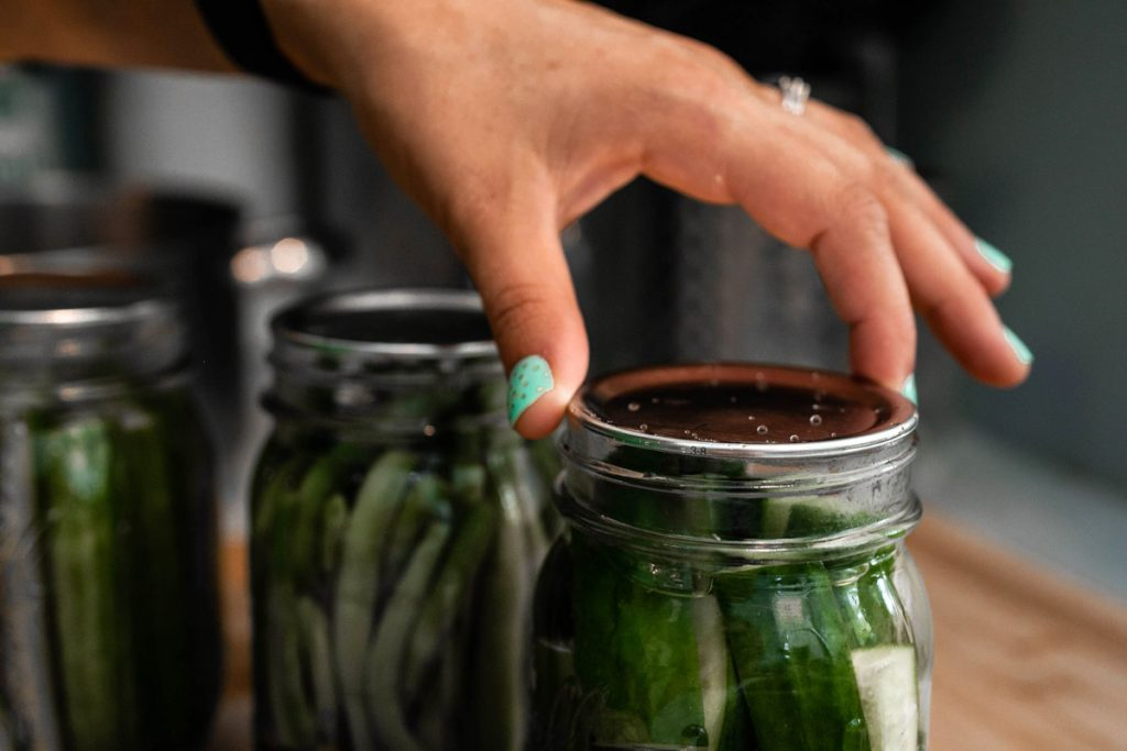 A person screws on the lid to a mason jar. Inside the jar are pickled vegetables.