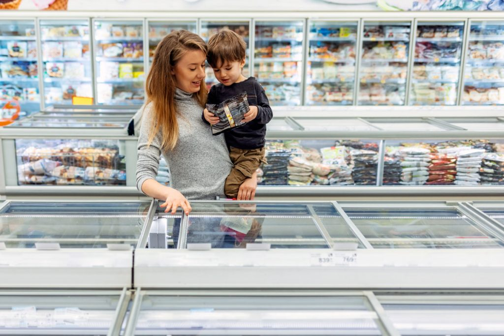 A woman and son shop in the frozen food isle at the grocery store. It is recommended to try purchasing frozen foods instead of fresh if you want to eliminate food waste.