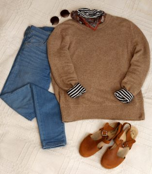 An outfit is folded to where you can see it in it's entirety. There's a brown sweater, scarf, sunglasses, blue jeans and brown wedges.