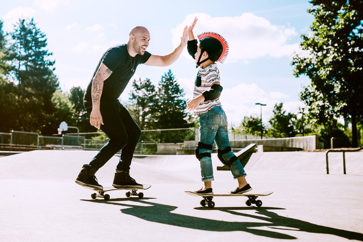A man high-fives his child while they both pass each other on skateboards.
