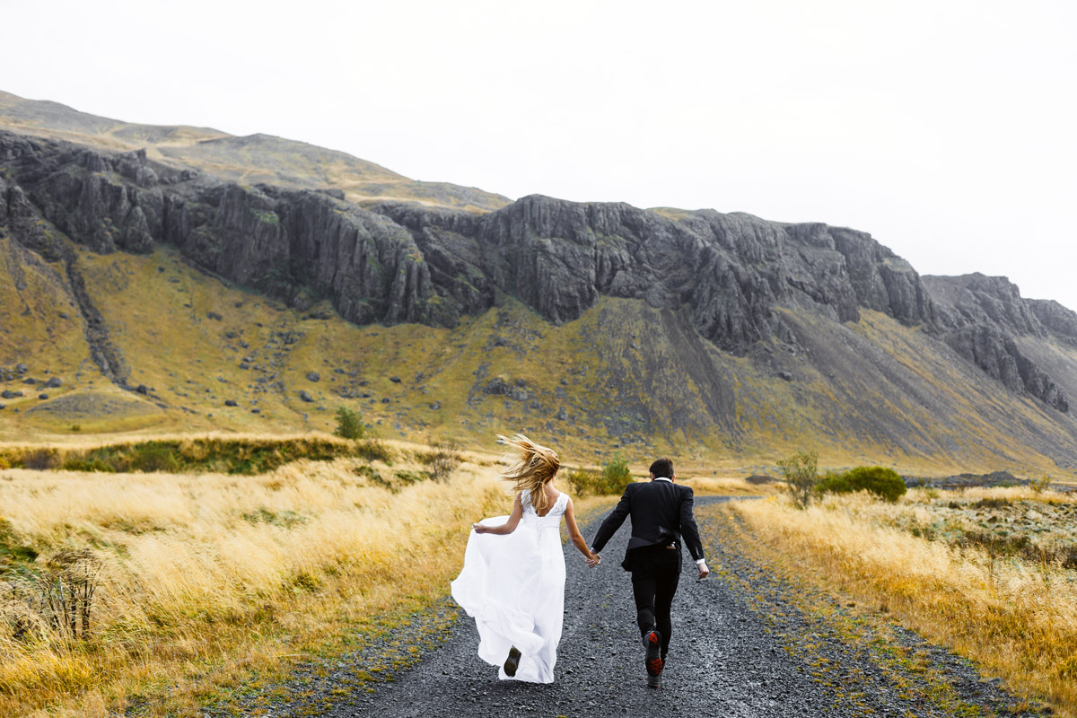 A newly wed couple run on a path toward a mountain while wearing a bridal gown and tux.